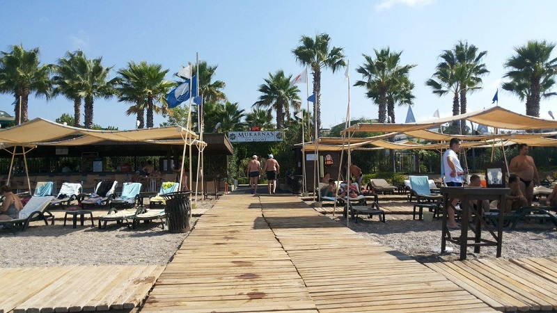 2-3. Вход в отель со стороны моря и пляжа. 4 ряда лежаков и длиииинные аля-зонтики